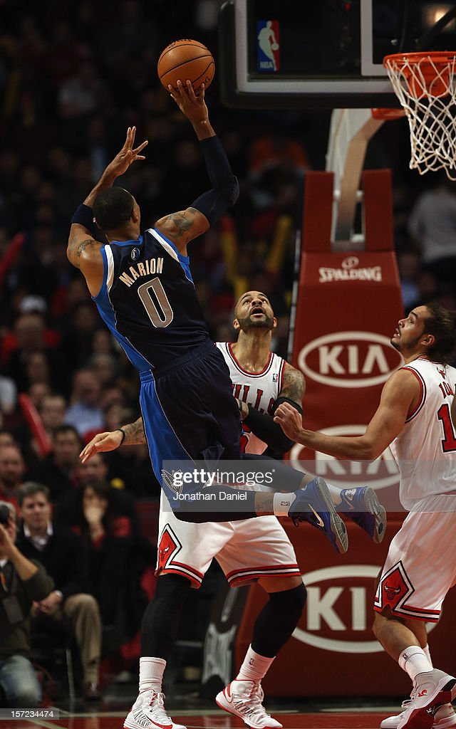 Shawn Marion #0 of the Dallas Mavericks shoots over Carlos Boozer #5 and Joakim Noah #13 of the Chicago Bulls at the United Center on November 28, 2012 in Chicago, Illinois. The Bulls defeated the Mavericks 101-78.