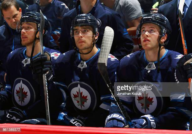 Shawn Matthias Brandon Tanev and Andrew Copp of the Winnipeg Jets look on from the bench prior to puck drop against the Carolina Hurricanes at the...