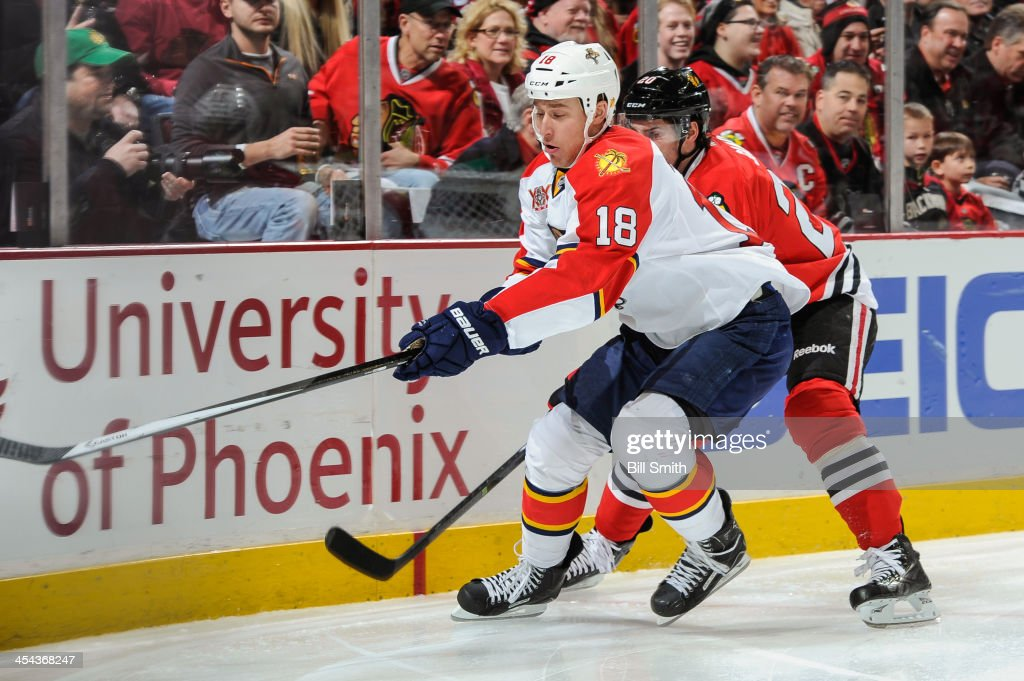 Shawn Matthias #18 of the Florida Panthers and <a gi-track='captionPersonalityLinkClicked' href=/galleries/search?phrase=Brandon+Saad&family=editorial&specificpeople=7128385 ng-click='$event.stopPropagation()'>Brandon Saad</a> #20 of the Chicago Blackhawks chase after the puck during the NHL game on December 08, 2013 at the United Center in Chicago, Illinois.