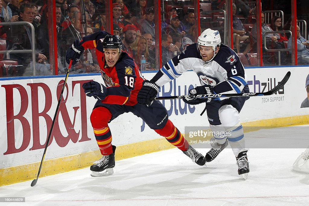 Shawn Matthias #18 of the Florida Panthers and Ron Hainsey #6 of the Winnipeg Jets pursue a loose puck at the BB&T Center on January 31, 2013 in Sunrise, Florida.