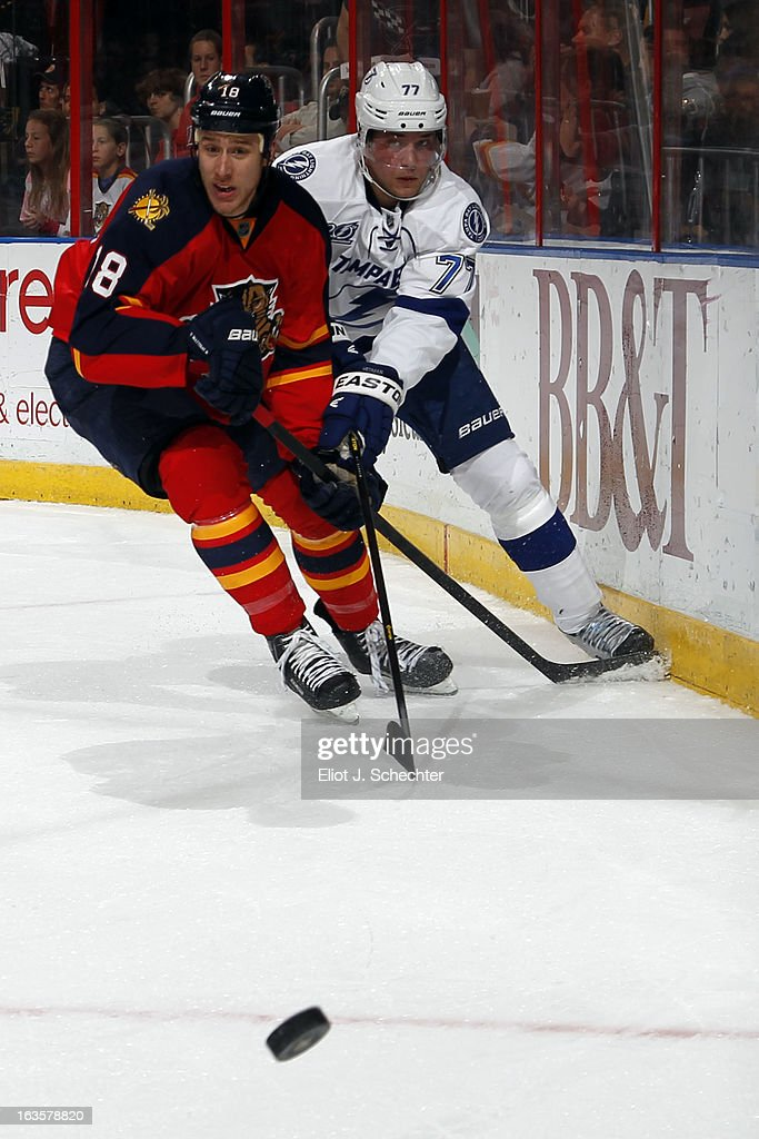 Shawn Matthias #18 of the Florida Panthers digs the puck out from the boards against Richard Panik #71 of the Tampa Bay Lightning at the BB&T Center on March 12, 2013 in Sunrise, Florida.