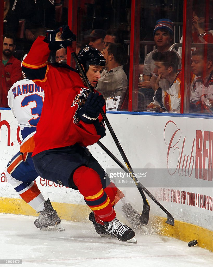 Shawn Matthias #18 of the Florida Panthers digs the puck out from the boards against Travis Hamonic #3 of the New York Islanders at the BB&T Center on March 16, 2013 in Sunrise, Florida.