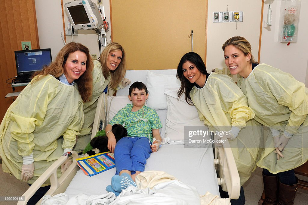 Shawn O'Brien, Kara Mankins, Anna Welker and Rosanne Gregory of the New England Patriots Women's Association visit Logan at Boston Children's Hospital on January 10, 2013 in Boston, Massachusetts.