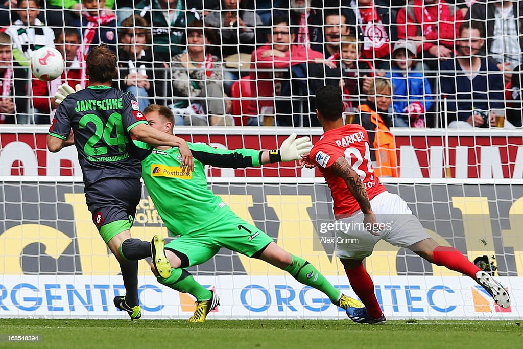 Shawn Parker of Mainz scores his team's first goal against goalkeeper <a gi-track='captionPersonalityLinkClicked' href=/galleries/search?phrase=Marc-Andre+ter+Stegen&family=editorial&specificpeople=5528638 ng-click='$event.stopPropagation()'>Marc-Andre ter Stegen</a> and <a gi-track='captionPersonalityLinkClicked' href=/galleries/search?phrase=Tony+Jantschke&family=editorial&specificpeople=4158344 ng-click='$event.stopPropagation()'>Tony Jantschke</a> of Moenchengladbach during the Bundesliga match between 1. FSV Mainz 05 and VfL Borussia Moenchengladbach at Coface Arena on May 11, 2013 in Mainz, Germany.