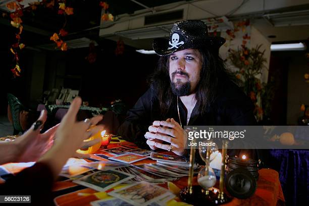 Shawn Poirier who calls himself a witch listens to Sue Larkin as she reads his tarot cards during a Psychic Fair October 27 2005 in Salem...