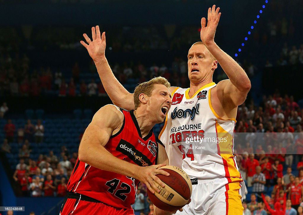 Shawn Redhage of the Wildcats drives to the basket against Adam Ballinger of the Tigers during the round 20 NBL match between the Perth Wildcats and the Melbourne Tigers at Perth Arena on February 21, 2013 in Perth, Australia.