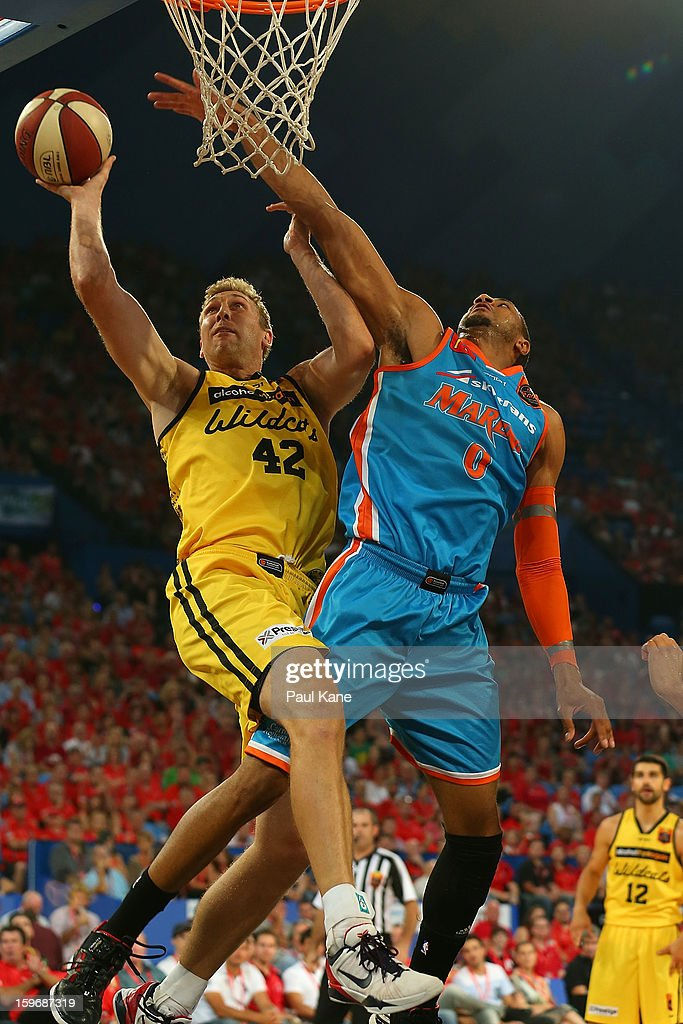 Shawn Redhage of the Wildcats drives to the basket against Shane Edwards of the Taipans during the round 15 NBL match between the Perth Wildcats and the Cairns Taipans at Perth Arena on January 18, 2013 in Perth, Australia.