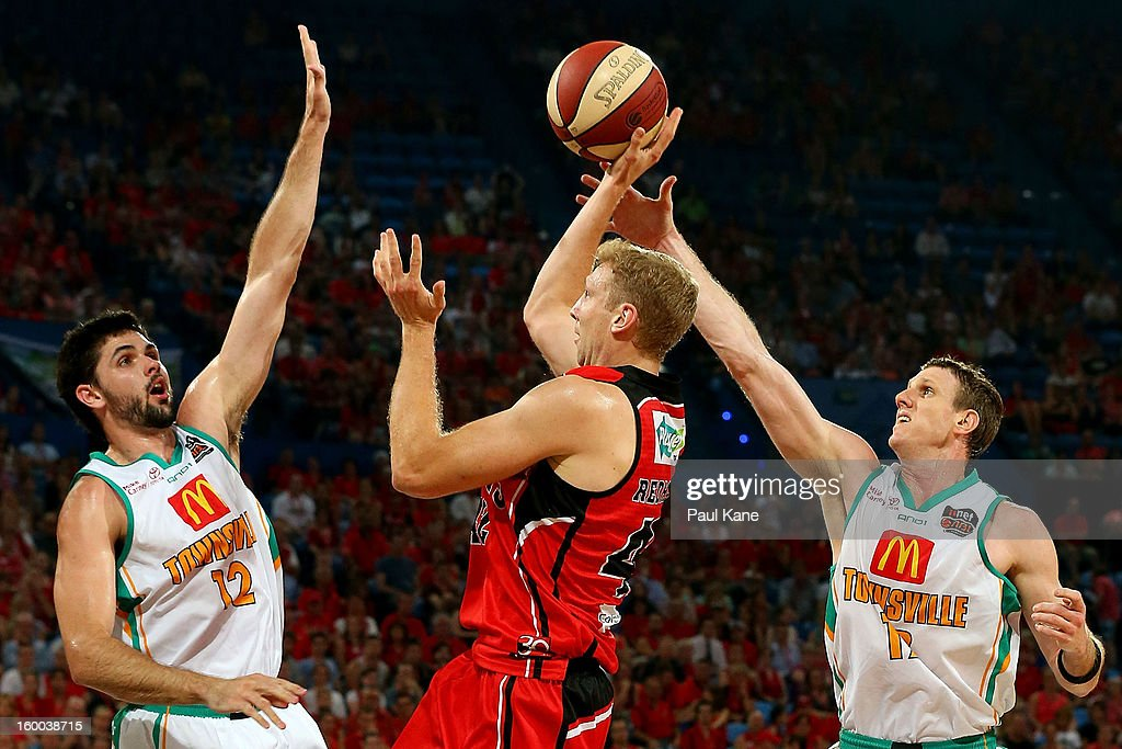 Shawn Redhage of the Wildcats lays up against Todd Blanchfield and Peter Crawford of the Crocodiles during the round 16 NBL match between the Perth Wildcats and the Townsville Crocodiles at Perth Arena on January 25, 2013 in Perth, Australia.