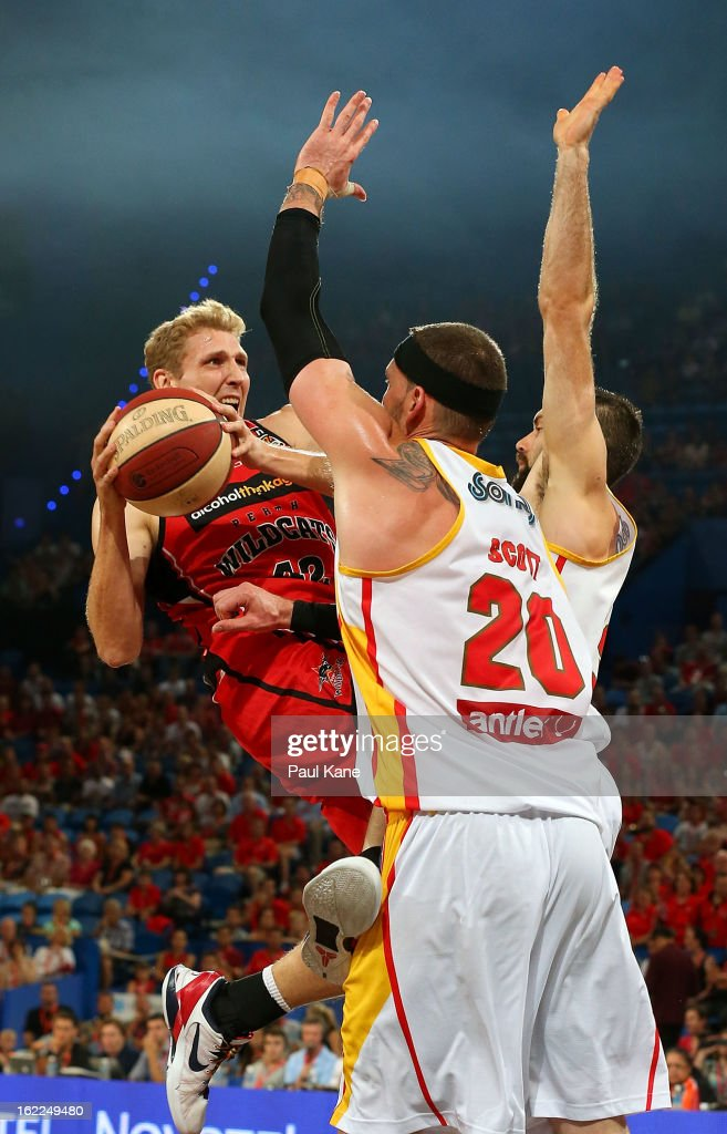 Shawn Redhage of the Wildcats looks to layup against Seth Scott and Liam Rush of the Tigers during the round 20 NBL match between the Perth Wildcats and the Melbourne Tigers at Perth Arena on February 21, 2013 in Perth, Australia.