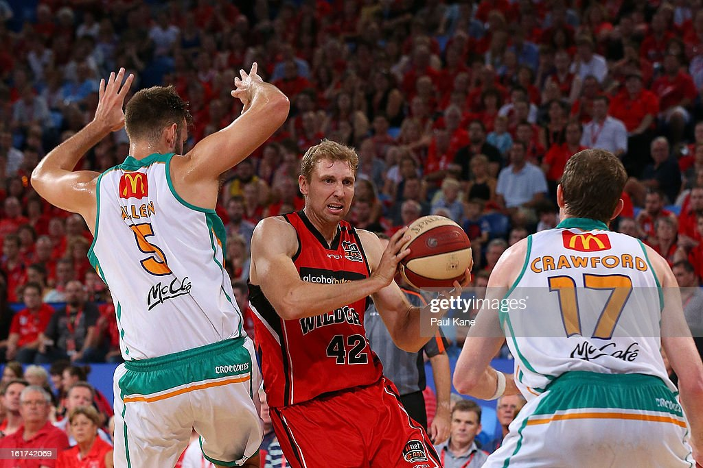 Shawn Redhage of the Wildcats looks to pass the ball against Ben Allen and Peter Crawford of the Crocodiles during the round 19 NBL match between the Perth Wildcats and the Townsville Crocodiles at Perth Arena on February 15, 2013 in Perth, Australia.