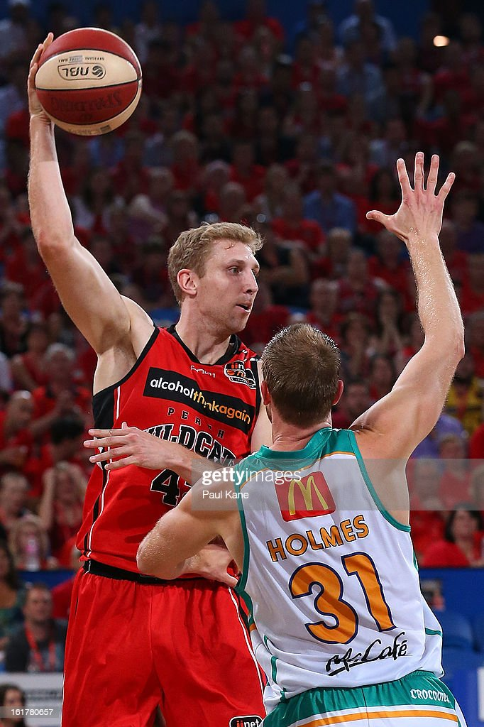 Shawn Redhage of the Wildcats passes the ball against Jacob Holmes of the Crocodiles during the round 19 NBL match between the Perth Wildcats and the Townsville Crocodiles at Perth Arena on February 15, 2013 in Perth, Australia.