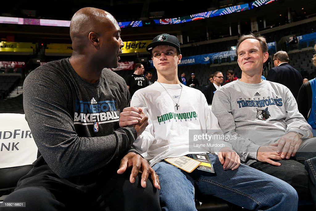 Shawn Respert, player development coach for the Minnesota Timberwolves, left, speaks with Cody Metz, center, and his father, who were in attendance through the Make-A-Wish Foundation, before a game between the Timberwolves and Oklahoma City Thunder on January 9, 2013 at the Chesapeake Energy Arena in Oklahoma City, Oklahoma.
