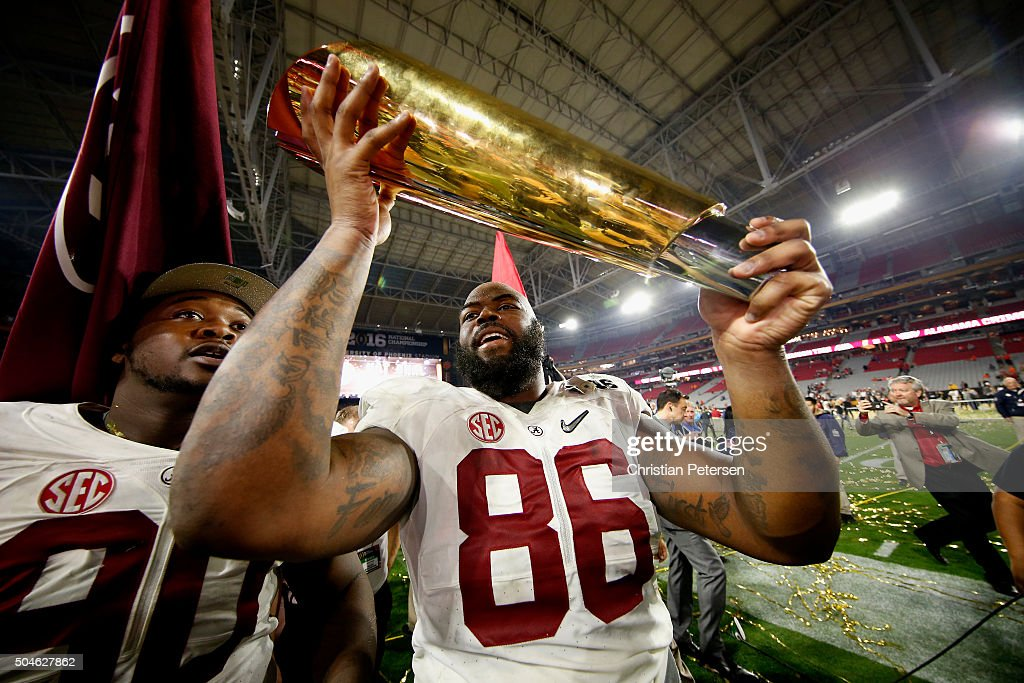 A'Shawn Robinson #86 of the Alabama Crimson Tide celebrates by hoisting the College Football Playoff National Championship Trophy after defeating the Clemson Tigers in the 2016 College Football Playoff National Championship Game at University of Phoenix Stadium on January 11, 2016 in Glendale, Arizona. The Crimson Tide defeated the Tigers with a score of 45 to 40.