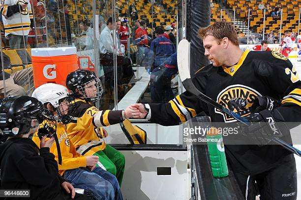 Shawn Thornton of the Boston Bruins greets fans on the bench during warmups before the game against the Montreal Canadiens at the TD Garden on...