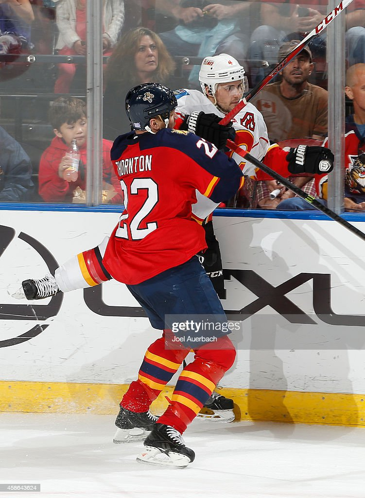 Shawn Thornton #22 of the Florida Panthers checks Kris Russell #4 of the Calgary Flames into the boards during third period action at the BB&T Center on November 8, 2014 in Sunrise, Florida. The Flames defeated the Panthers 6-4.