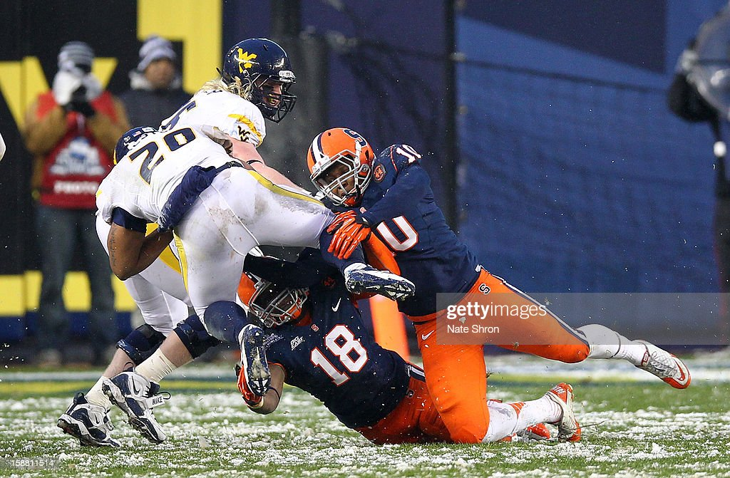 Shawne Alston #20 of the West Virginia Mountaineers runs the ball as he is tackled by Siriki Diabate #18 and Markus Pierce-Brewster #10 of the Syracuse Orange during the New Era Pinstripe Bowl at Yankee Stadium on December 29, 2012 in the Bronx borough of New York City.
