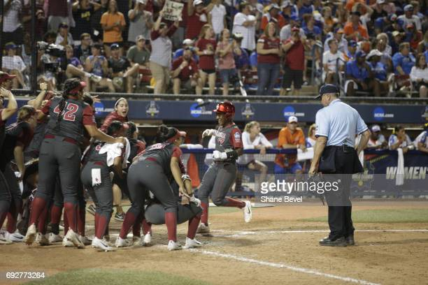 Shay Knighten of the University of Oklahoma meets her teammates at home plate after scoring a run against the University of Florida during Game 1 of...