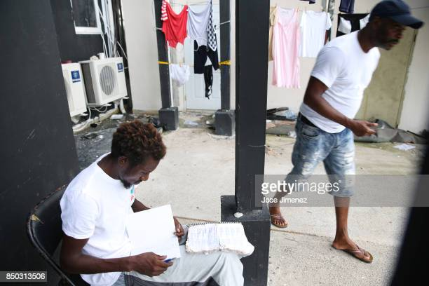Shaz Charles a fisherman who lost his boat to Hurricane Irma writes his navigations charts in a dry notebook at a shelter in the Sir Vivian Richards...