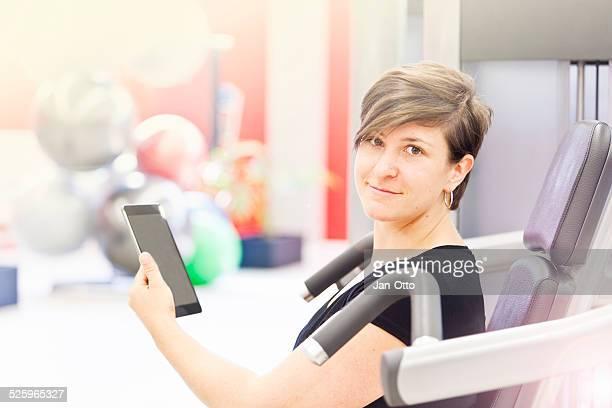 Elle son vérifiant son trainingsplan sur une tablette PC