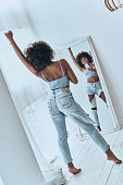 Full length rear view of beautiful young African woman listening music and smiling while taking selfie at home
