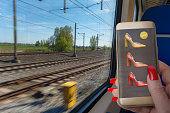 personal perspective mature woman on train in motion using her smartphone to buy heels image on phone by contributor