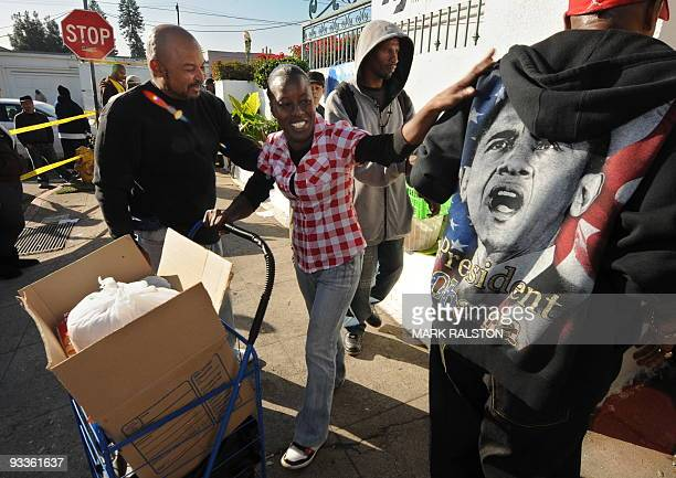 Shea Christopher receives her handouts from a volunteer wearing a President Obama jacket as part of a group of 10000 lowincome and needy people who...