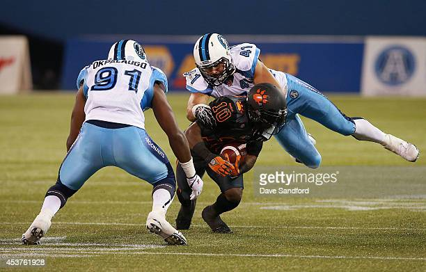 Shea Emry of the Toronto Argonauts makes a tackle on Stefan Logan of the BC Lions during their game at Rogers Centre on August 17 2014 in Toronto...