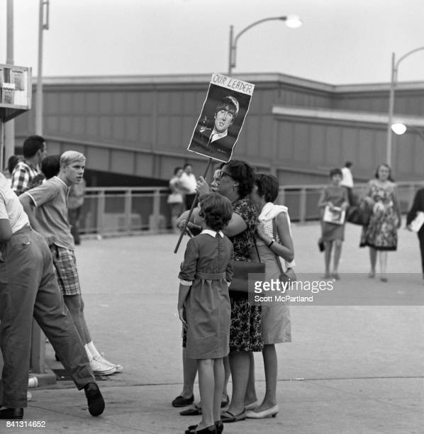 A mother holding a 'John Lennon Our Leader' sign stands beside her three daughters prior to seeing The Beatles live in concert on their last American...