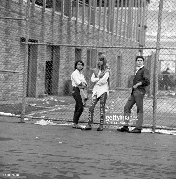 three somber looking fans unable to attend the Beatles concert stand by a fence around the back of Shea Stadium