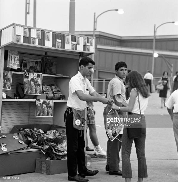 Two vendors sell Beatles merchandise to a female fan in the parking lot of Shea Stadium prior to the band hitting the stage on their last American...