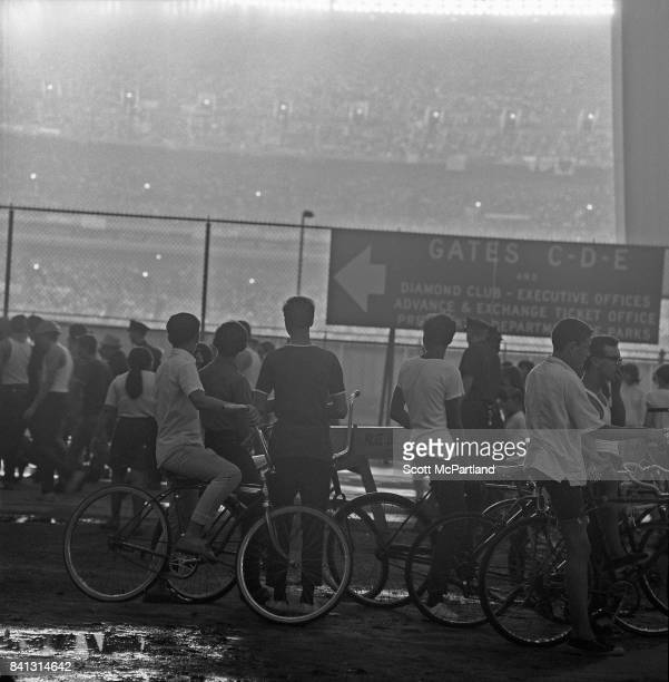 Young fans on their bicycles unable to enter Shea Stadium try to catch a glimpse of The Beatles over a fence on the outside of the stadium