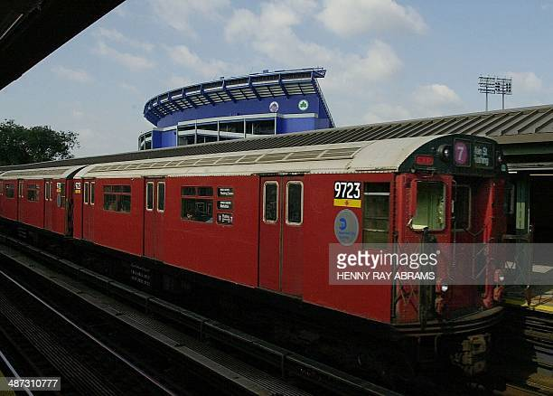 Shea Stadium the home of the National League Champion New York Mets looms in the background behind a train on the number '7' line as it leaves the...