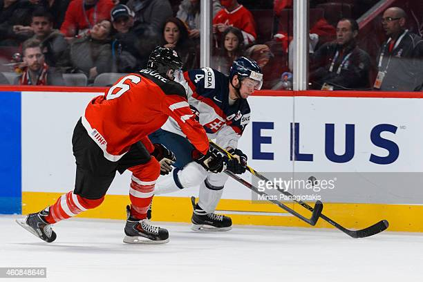 Shea Theodore of Team Canada defends against Mislav Rosandic of Team Slovakia during the 2015 IIHF World Junior Hockey Championship game at the Bell...