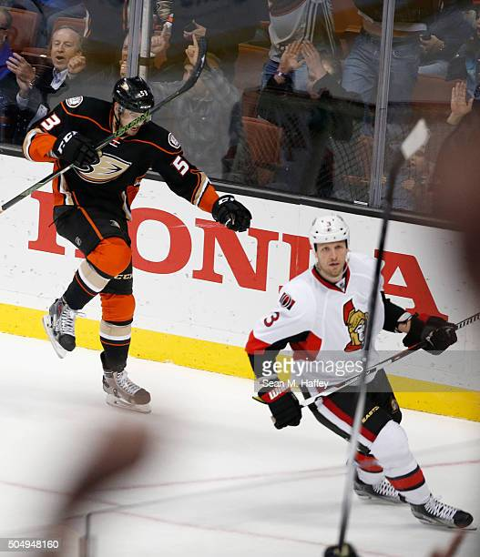 Shea Theodore of the Anaheim Ducks reacts to scoring a goal against the Ottawa Senators Marc Methot of the Ottawa Senators looks on during the third...