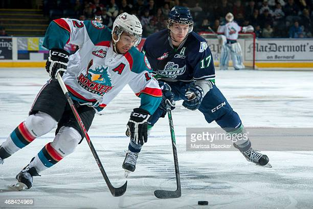Shea Theodore of the Seattle Thunderbirds stick checks Tyrell Goulbourne of the Kelowna Rockets during the first period on February 10 2014 at...