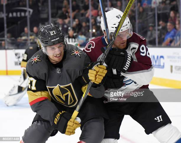 Shea Theodore of the Vegas Golden Knights and Gabriel Landeskog of the Colorado Avalanche crash into each other as they chase the puck in the third...