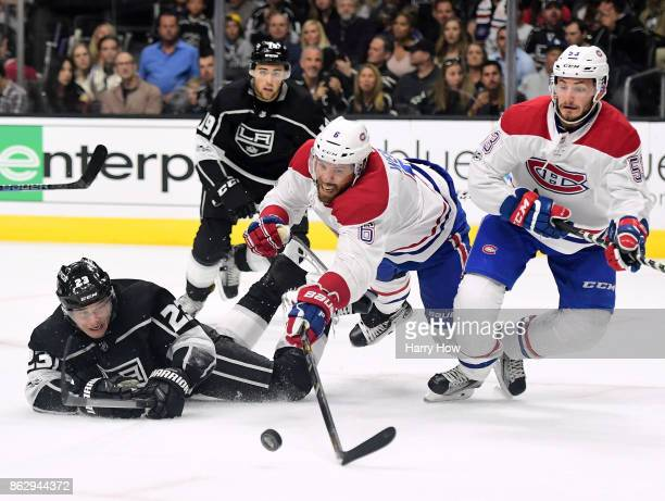 Shea Weber of the Montreal Canadiens and Dustin Brown of the Los Angeles Kings dive for the puck as Victor Mete looks on during the second period at...