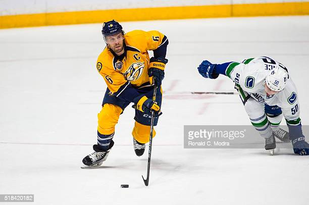 Shea Weber of the Nashville Predators skates with the puck against Brendan Gaunce of the Vancouver Canucks during a NHL game at Bridgestone Arena on...