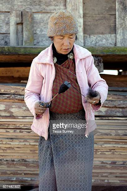 Sheep farmer Namgay Zam spins wool using a drop spindle called a Yoekpa Chubja Bhutan With the easy availability of commercially processed wool and...