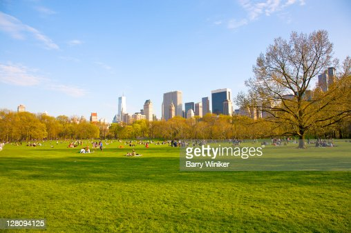 Sheep Meadow in late afternoon in spring, with office towers of Midtown, Central Park, New York, New York : Foto de stock