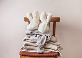 stack of warm clothes on the chair, Pair of warm winter sheepskin slippers