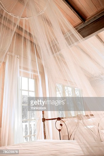 A sheer white canopy hanging over a bed stock photo for Hanging canopy over bed