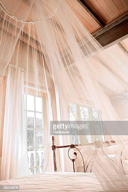 A sheer white canopy hanging over a bed.