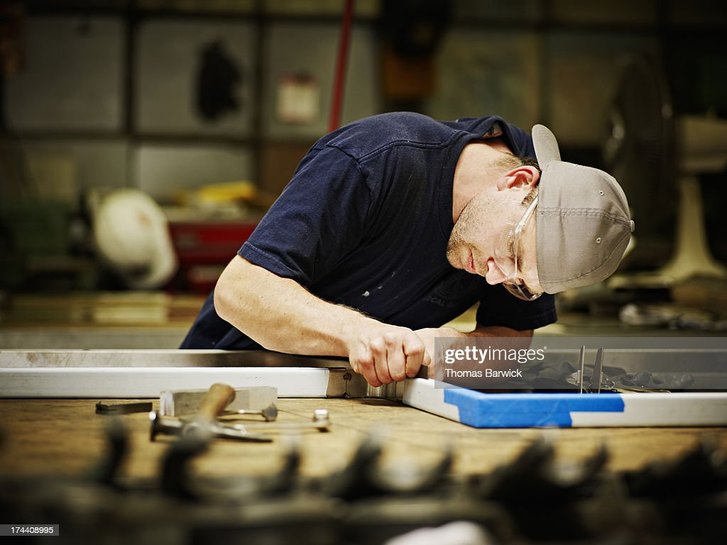 Sheet metal worker checking accuracy of weld : Stock Photo