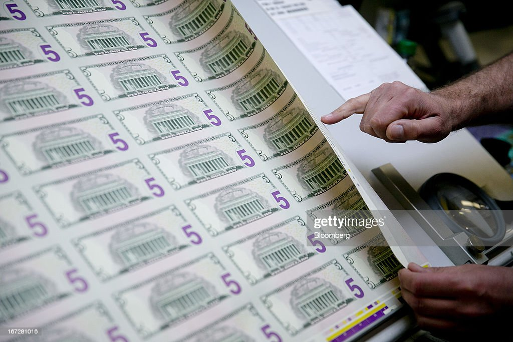 A sheet of five dollar notes not yet fully printed is inspected by employees at the Bureau of Engraving and Printing in Washington, D.C., U.S., on Tuesday, April 23, 2013. Stocks rallied amid growth in U.S. home sales, better-than-forecast earnings and speculation the European Central Bank will cut interest rates. U.S. equities recovered after briefly erasing gains following a false report of explosions at the White House. Photographer: Andrew Harrer/Bloomberg via Getty Images