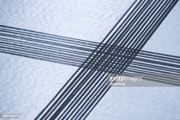 A sheet of woven glass and carbon travels through a machine in the research and development center at the Open Hybrid Lab Factory in Wolfsburg...