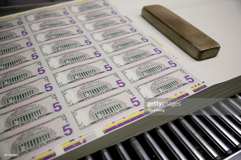 Sheets of five dollar notes are fed through a sorting machine at the Bureau of Engraving and Printing in Washington, D.C., U.S., on Tuesday, April 23, 2013. Stocks rallied amid growth in U.S. home sales, better-than-forecast earnings and speculation the European Central Bank will cut interest rates. U.S. equities recovered after briefly erasing gains following a false report of explosions at the White House. Photographer: Andrew Harrer/Bloomberg via Getty Images