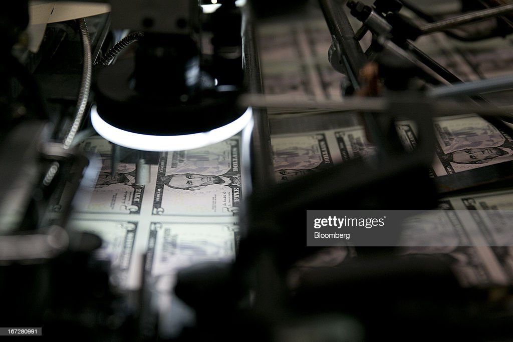 Sheets of five dollar notes go through a machine to receive a serial number and the seals of the U.S. Treasury and Federal Reserve at the Bureau of Engraving and Printing in Washington, D.C., U.S., on Tuesday, April 23, 2013. Stocks rallied amid growth in U.S. home sales, better-than-forecast earnings and speculation the European Central Bank will cut interest rates. U.S. equities recovered after briefly erasing gains following a false report of explosions at the White House. Photographer: Andrew Harrer/Bloomberg via Getty Images