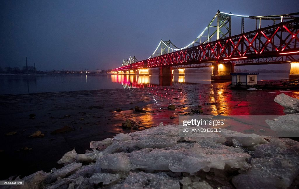 Sheets of ice are seen next to the bridge on the banks of the Yalu River at the Chinese border town of Dandong across from the North Korean town of Sinuiju on February 8, 2016. The UN Security Council strongly condemned North Korea's rocket launch on February 7 and agreed to move quickly to impose new sanctions that will punish Pyongyang for 'these dangerous and serious violations.' AFP PHOTO / JOHANNES EISELE / AFP / JOHANNES EISELE