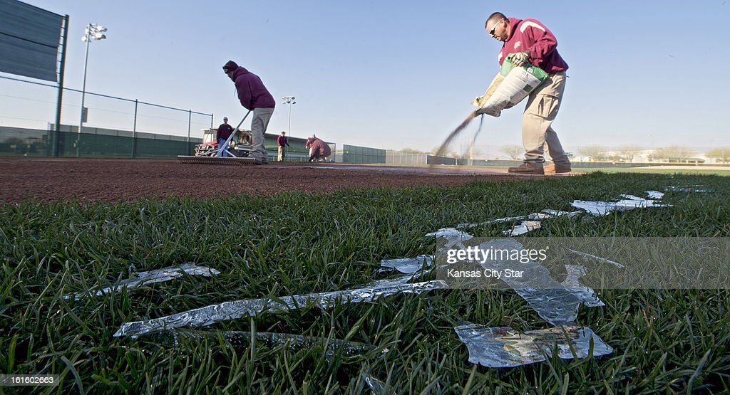 Sheets of ice that had formed overnight on the home plate covering begin to melt as the grounds crew dries out the home plate area before a Kansas City Royals' spring training workout in Surprise, Arizona, Tuesday, February 12, 2013.